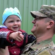 A soldier holds his young son.