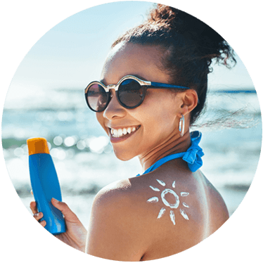 woman holding sunscreen at beach