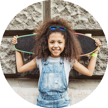 female child smiling and holding a skateboard