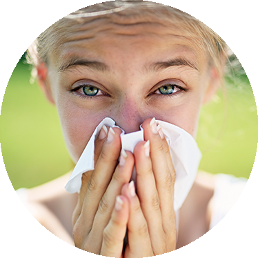 a woman blowing her nose during allergy season.